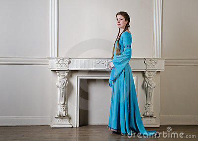 Yound woman in historical dress near fireplace