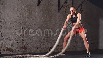 Young adult girl practising battle rope exercise during a cross fit workout at the gym,. Young adult girl practising battle rope exercise during a cross fit stock video