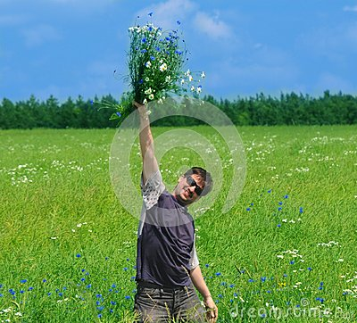 Young adult man with bouquet of wildflowers