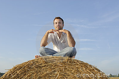 Young adult sitting on a straw bale