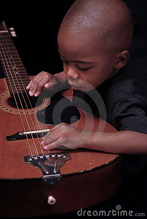 Young African american boy plays the guitar