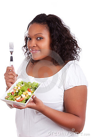 Young african american woman eating salad