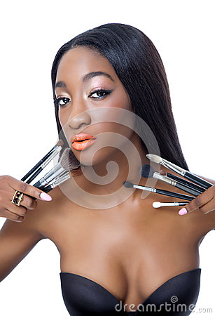 Young African beauty with make up brushes