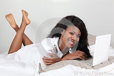Young Afro woman laid in front of a laptop