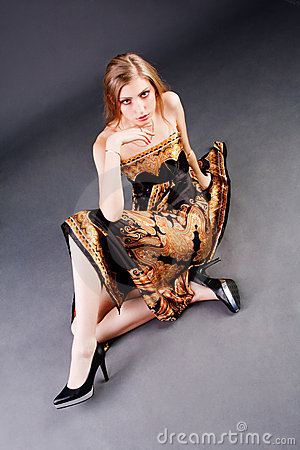 Young alluring girl in dress which sits on floor