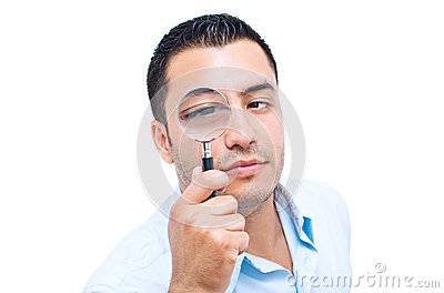 Young amazed man looking with magnifier