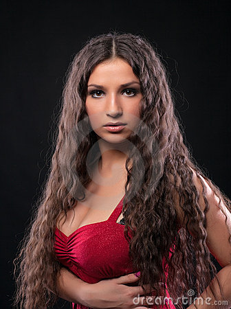 Young amazing girl with curly hair in red