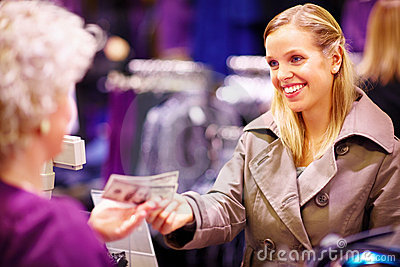 Young american woman paying with US dollar bills