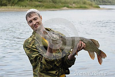 Young angler holds and looks at the big pike