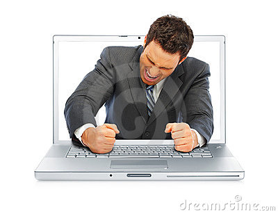 Young angry business man througfh a laptop