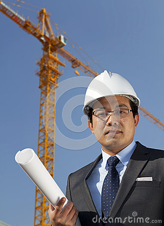 Young architect standing under yellow crane building site