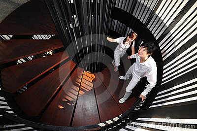 Young Asian Couple in Love climbing spiral stairs