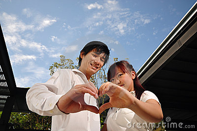 Young Asian Couple in Love forming a heart shape