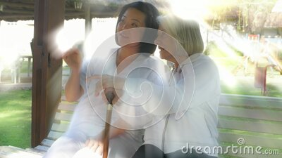 Young asian female doctor assisting elderly woman seating on hospital garden bench. Light rays from behind stock video
