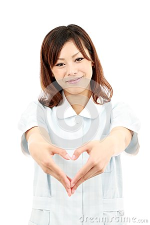 Young asian female nurse shows fingers heart
