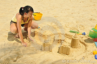 Young Asian Girl Building Sandcastle By The Beach