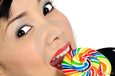 Young asian girl eating lollipop