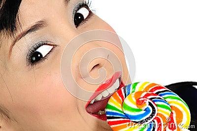 Young asian girl eating lollipop