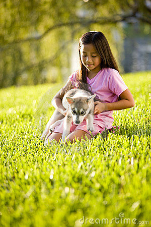 Young Asian girl holding puppy sitting on grass