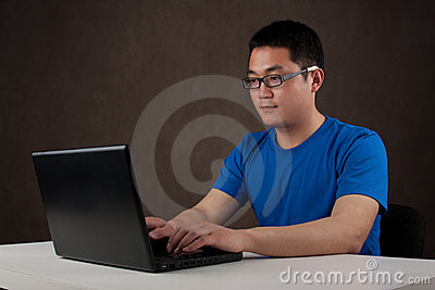 Young asian man working on his laptop computer