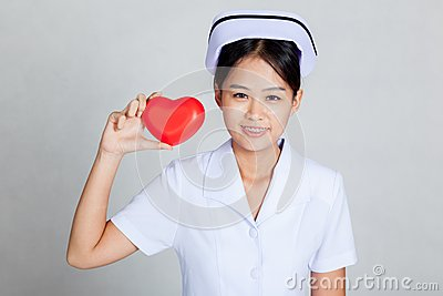 Young Asian nurse show red heart