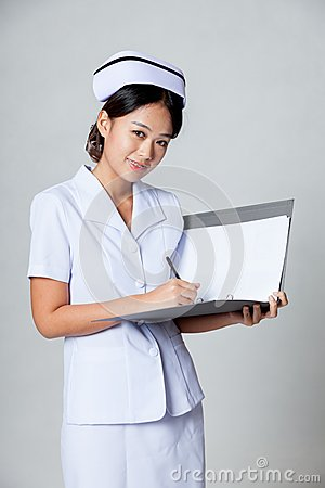 Young Asian nurse smile working on a report