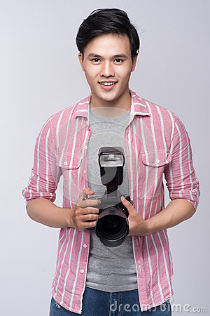 Free Young Asian Photographer Holding Digital Camera, While Working I Royalty Free Stock Photos - 92520978