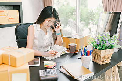 Young Asian small business owner working at home office, using mobile phone and taking note on purchase orders Stock Photo