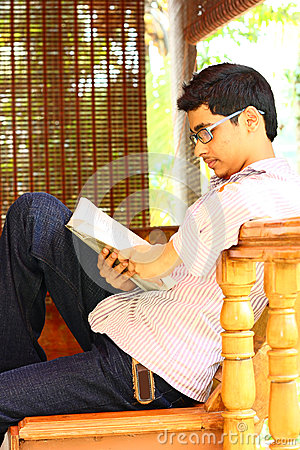 Young Asian Student Sitting and Reading Textbook