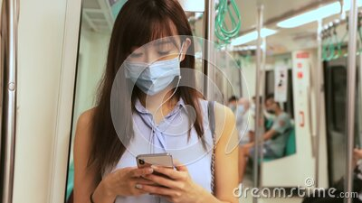 Young Asian woman passenger wearing surgical mask and listening music via mobile phone in subway train stock video footage
