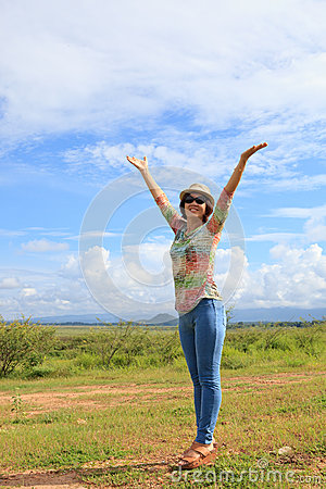 Young asian woman standing in field and rising up her hand with nice emotion