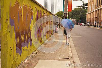 Young Asian woman walking with umbrella