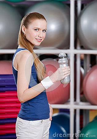Young athletic woman in sportswear holds a water bottle