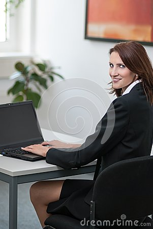 Young attractice businesswoman uses her laptop