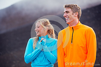 Young attractive athletic couple, wearing sporty cloths on trail