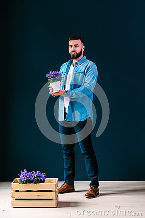 Free Young Attractive Bearded Hipster Man,dressed In Denim Shirt And Blue Pants, Stands Indoors, Holding Pot Of Flower Stock Images - 88814614