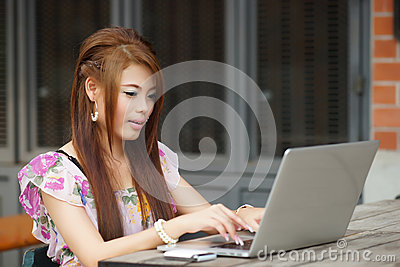 Young attractive business woman working on her laptop at outdoor
