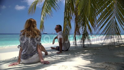 Young attractive couple enjoying a holiday on the tropical coast. The date on the ocean. An attractive young woman and a handsome man enjoying a holiday on the stock video footage