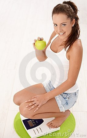 Young attractive female squatting on scale smiling