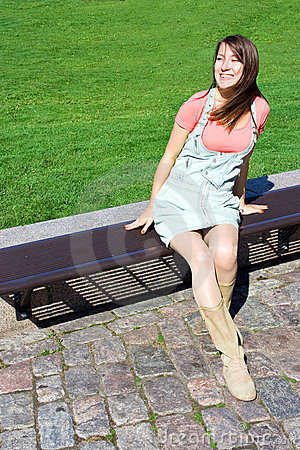 Young attractive girl model sitting on bench