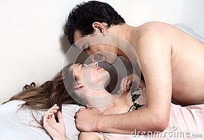 Young attractive happy couple in bedroom