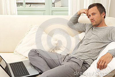 Young attractive man on couch with laptop at home.