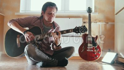 Young attractive musician plays the guitar sitting on the floor in the kitchen. Close up stock footage