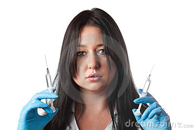 Young attractive nurse holding two syringes