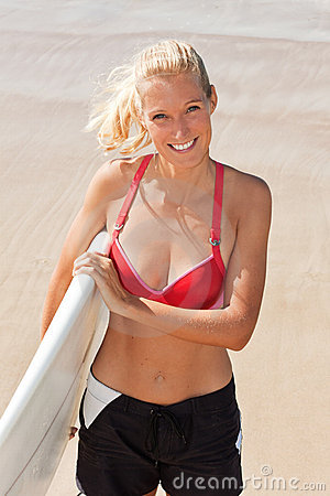 Young attractive surfer smiles on the beach