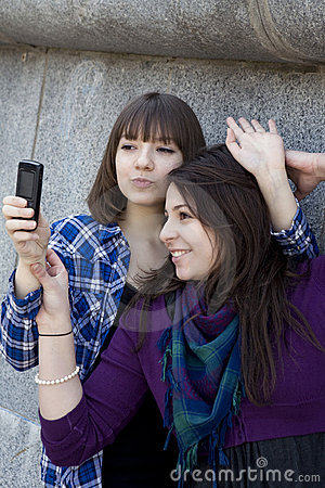 Young attractive teen girls take pictures by phone