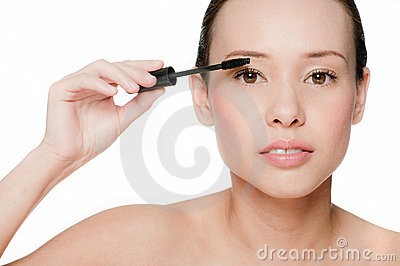 Young and attractive woman applying mascara