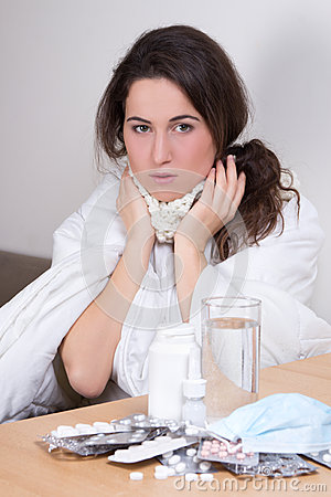 Young attractive woman fighting sickness with pills