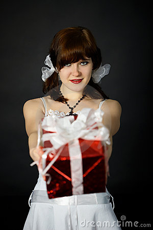 Young attractive woman gives a gift in red box