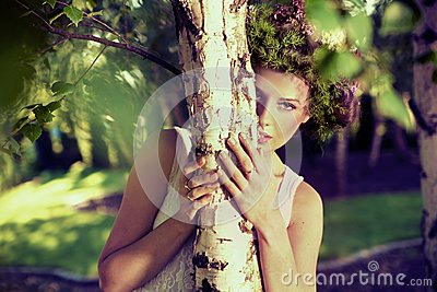 Young attractive woman hiding herself in forest